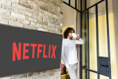 KYIV, UKRAINE - APRIL 25, 2020: young man in pajamas drinking coffee while standing near lcd screen with Netflix website