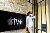 KIEW, UKRAINE - 25. April 2020: Junger Mann im Schlafanzug trinkt Kaffee, während er neben grünem LCD-Bildschirm mit Apple TV steht