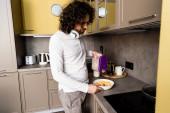 kudrnatý muž s bezdrátovými sluchátky na krku přidávání vloček do misky při přípravě snídaně