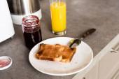 talíř s chutnými tousty a lžičkou u sklenice s džemem a sklenicí s pomerančovým džusem