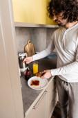 kudrnatý mladý muž v pyžamu pomazáním marmelády na toast k snídani