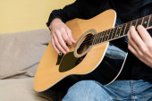 Photo Cropped view of man playing acoustic guitar on sofa at home