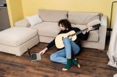 Hezký muž drží akustickou kytaru a pomocí notebooku na podlaze doma