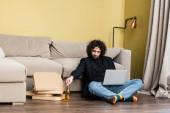 Freelancer drží láhev piva v blízkosti notebooku a pizza boxy na podlaze v obývacím pokoji