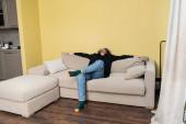 Lockiger Mann schaut auf, während er auf Couch im Wohnzimmer sitzt