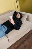 Kudrnatý muž se dívá na kameru a drží smartphone na gauči