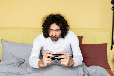 KYIV, UKRAINE - APRIL 25, 2020: concentrated, curly man playing video game with joystick in bedroom stock vector