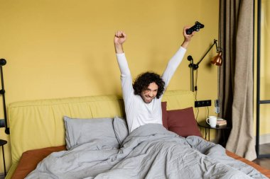 KYIV, UKRAINE - APRIL 25, 2020: happy young man showing winner gesture while playing video game in bed stock vector