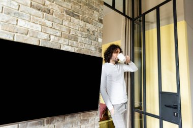 Young man in pajamas drinking coffee while standing near blank lcd screen hanging on brick wall stock vector