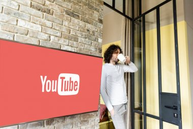 KYIV, UKRAINE - APRIL 25, 2020: young man in pajamas drinking coffee while standing near green lcd screen with Youtube website stock vector