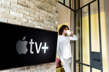 KYIV, UKRAINE - APRIL 25, 2020: young man in pajamas drinking coffee while standing near green lcd screen with Apple TV stock vector