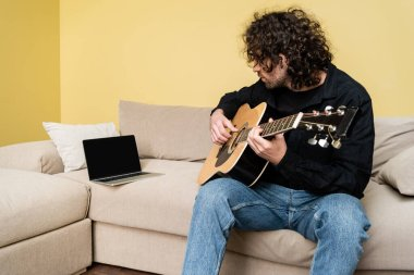 Man playing acoustic guitar during webinar on couch