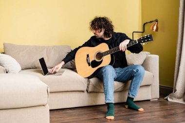 Curly man holding acoustic guitar and using laptop during online education in living room