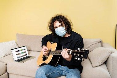 KYIV, UKRAINE - 25 Nisan 2020: Medikal maskeli adam dizüstü bilgisayarın yanında akustik gitar çalıyor