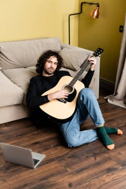 Handsome man holding acoustic guitar and looking at camera near laptop on floor