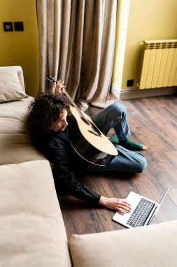 Overhead view of man holding acoustic guitar and using laptop during webinar on floor at home