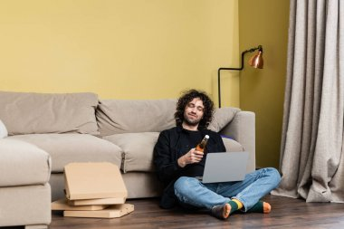 Selective focus of man holding beer bottle near laptop and pizza boxes on floor at home stock vector