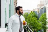 boční pohled na šťastný africký Američan drží láhev piva na balkóně