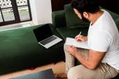 szakállas afro-amerikai férfi írás notebook közelében laptop üres képernyőn, tanulmány online koncepció