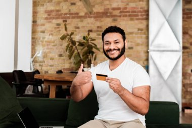 Happy african american man holding credit card near laptop with blank screen while showing thumb up stock vector