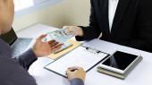 Podnikatelé dávají dolary na úplatky zaměstnancům při podepisování smluv na nákup nelegální půdy a nemovitostí, Podvody v podnikání a sociální nespravedlnost, korupce a úplatkářství koncept.