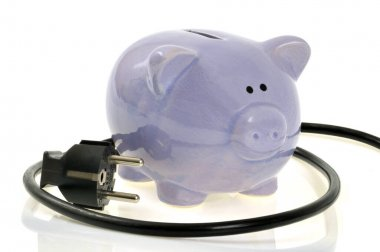 Electricity spending concept with a piggy bank surrounded by an electric wire close-up on a white background