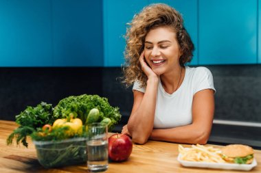 Beautiful woman with healthy green food at modern kitchen