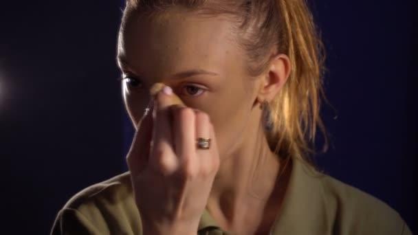 dívka stojí u zrcadla a zvukový základ na obličej