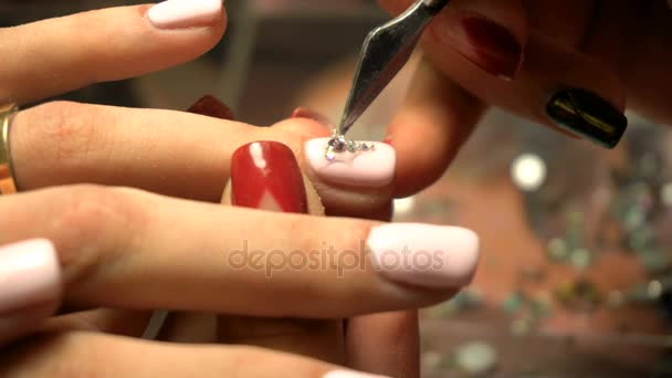girl makes a beautiful manicure with a pattern of stones for nails