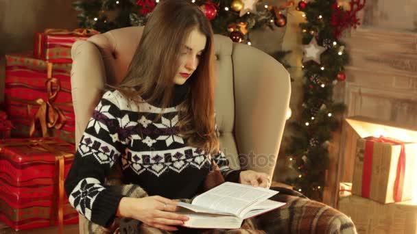 dívka sedí v křesle a čte knihu v místnosti vánoční