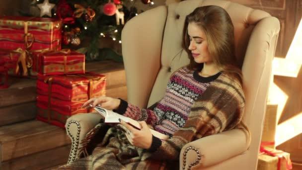 dívka v křesle s úsměvem a čtení knihy u vánočního stromu