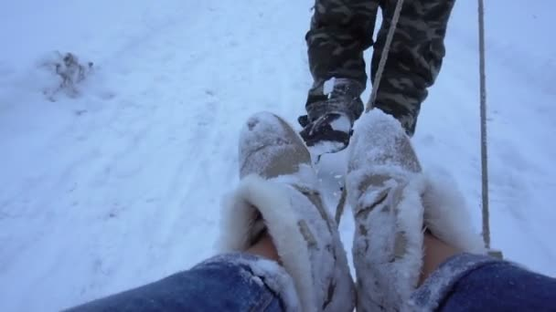 man rolls a girl on a sled in the snow