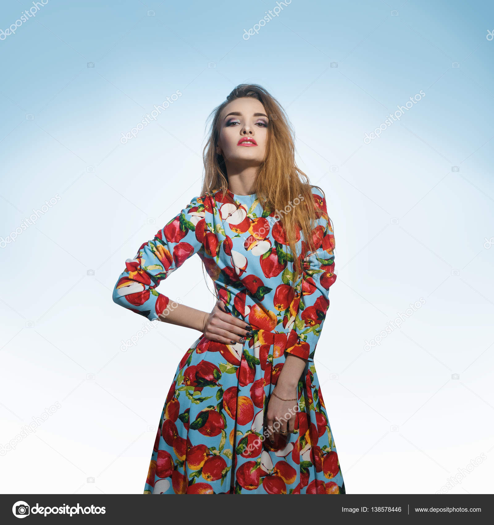 c9baa0a71c0d10 Sexy young girl in a bright dress keeps her hand on the side and stares  into the camera — Photo by ...