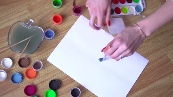girl draws a brush on paper with bright colors