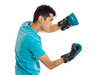 sports man posing in blue shirt and boxing gloves isolated on white background in studio