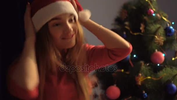 krásná mladá dáma v klobouku santa tančí a usmívá se. Vánoční nálada