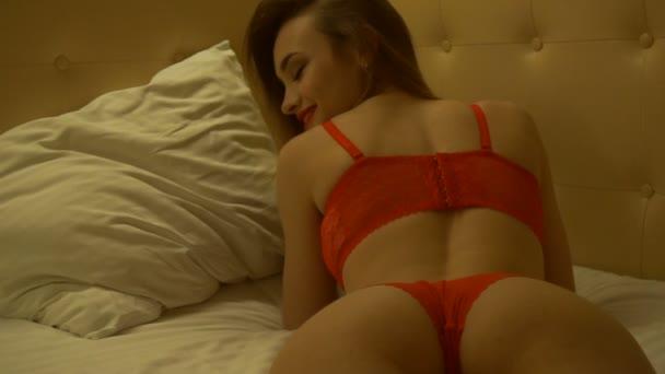 Smyslná mladá dáma s krásné kulaté zadek ležící na břiše v červené spodní prádlo