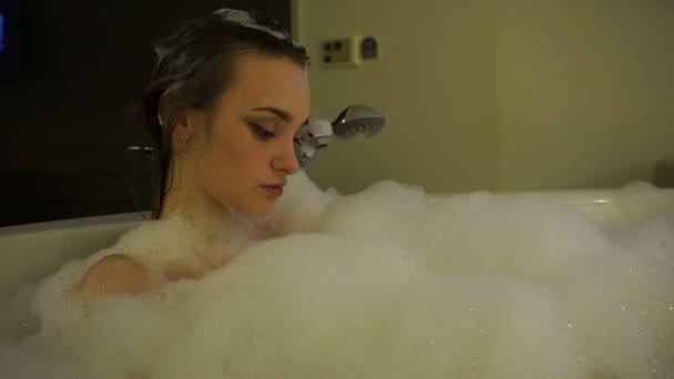 Roztomilá mladá žena koupající se v horké vaně s pěnou