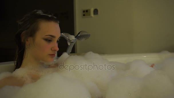 atraktivní mladá žena koupající se v horké vaně s pěnou