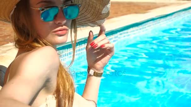 lány a szalma kalap és napszemüveg napozhatnak és úszhatnak a medencében