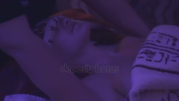 mladá dívka leží pod ručníky na masážní stůl, zatímco ji masíruje