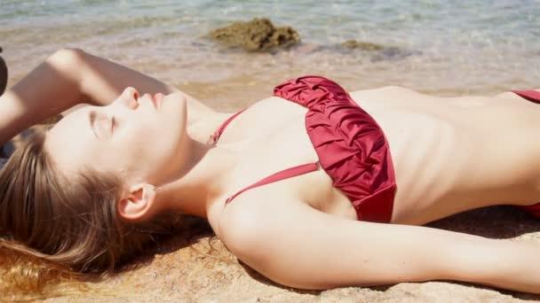 Szexi fiatal lány piros fürdőruhát, hazudik és napozás