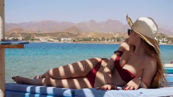 mladá sexy dívka v plavkách se nachází u moře na pláži ve stínu