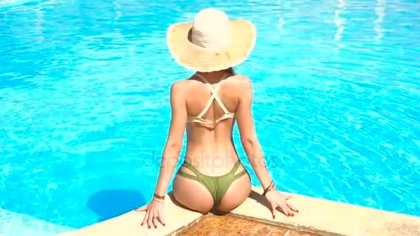 mladá dívka s sexy zadek v plavkách sedí u bazénu