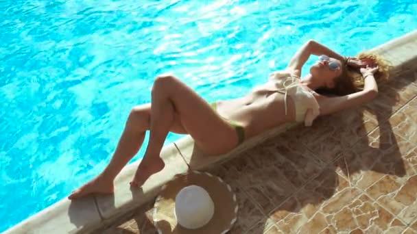 Modelka v sexy plavkách ležet a opalovat u bazénu 2.část v letní době