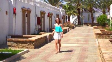 f9329d8a2d1fd1 Mooie meisje in bril en rok stappen op zomer Street en rechtzetten haar —  Stockvideo