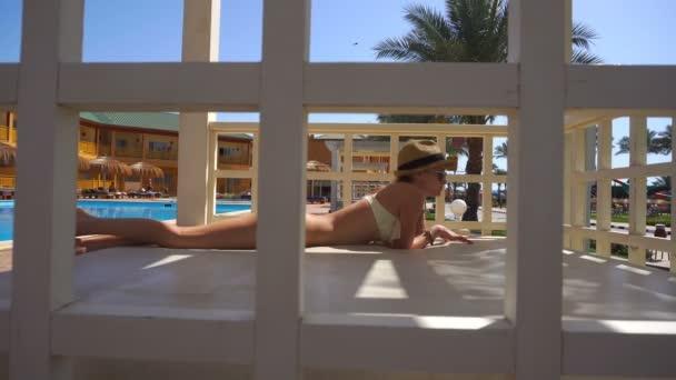 Szalma kalap és napszemüveg a medence partján fekvő szexi hölgy