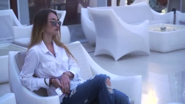 lady in white clothes sits outdoors in chair