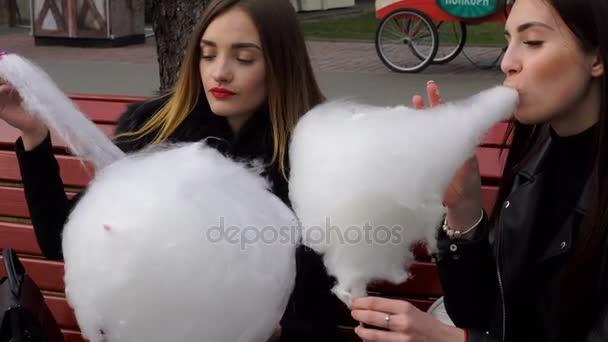 dvě vtipné přítelkyně jedí cukrovou vatu na ulici