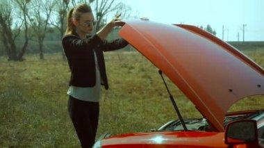 Cute girl closes the hood of the car